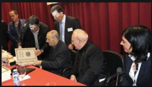 Don Enrique, junto al rector y la alcaldesa, ojea una edición especial de su última obra, obsequio de los asistentes al homenaje.
